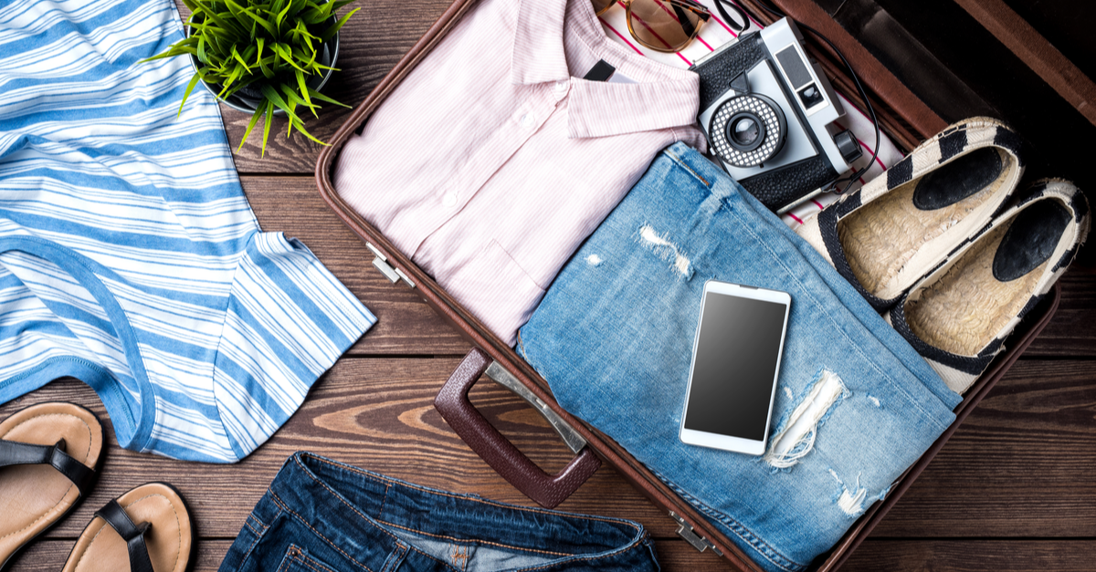 A pink shirt, jeans, shoes, a smarphone and a camera inside an open travel suitcase.