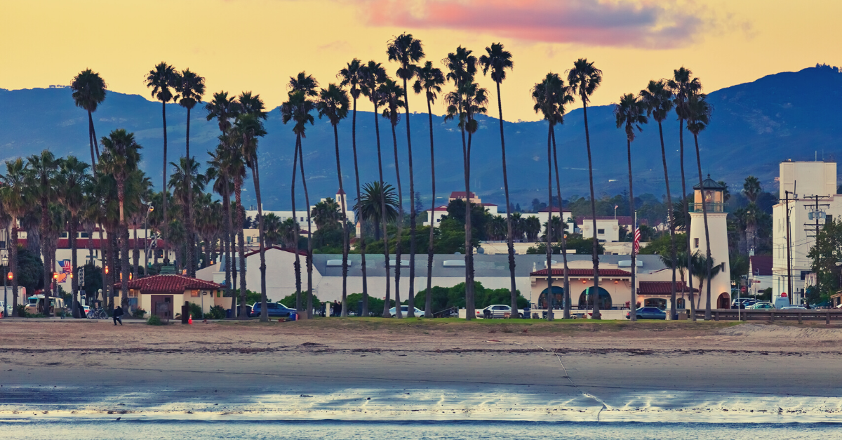View of the Santa Barbara coastline with mountains and palm trees during sunset.