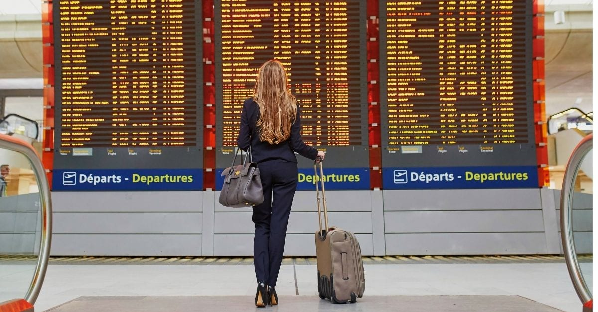 Woman checking the departures table on the airport with her carry on luggage on hand.