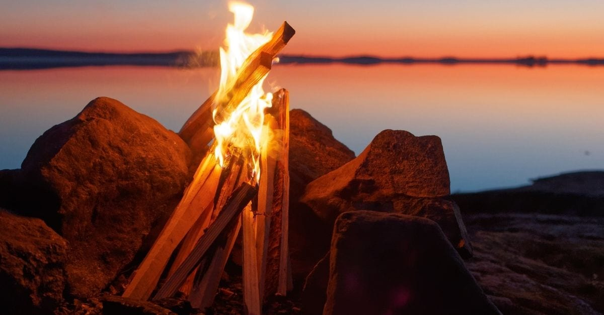 A bonfire by a lake during a red sunset.
