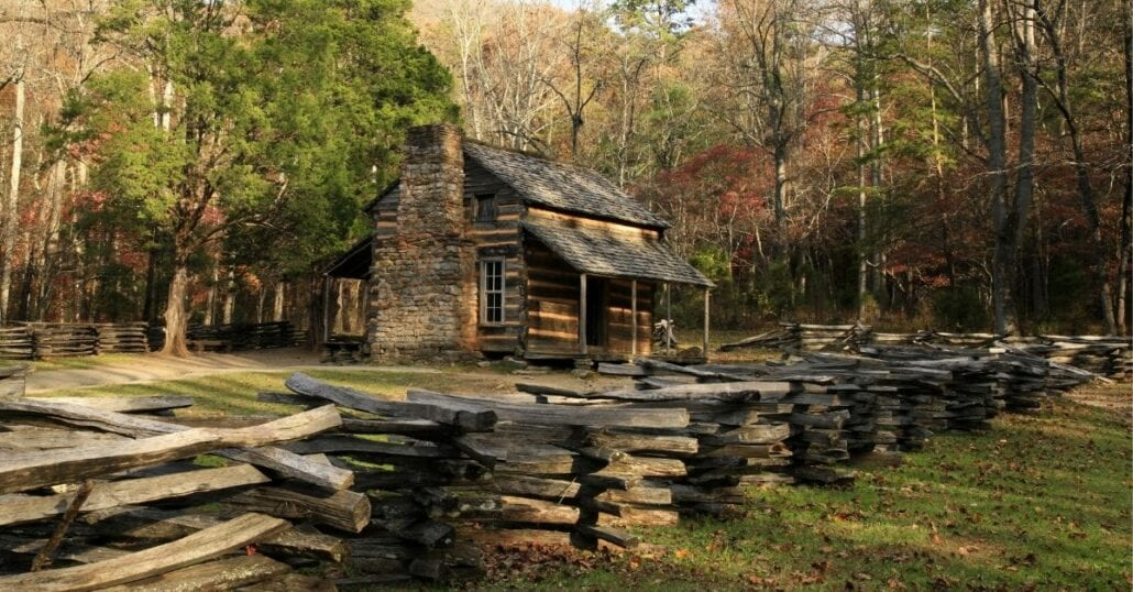 A woord and stone cabin surrounded by big trees during the fall season.