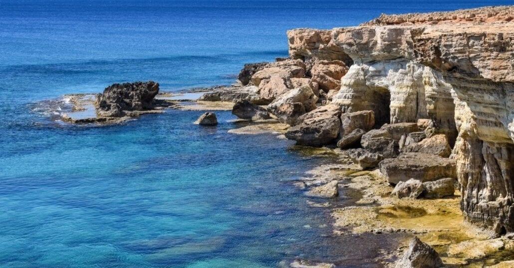 A rock cliff near the blue ocean in Cyprus.