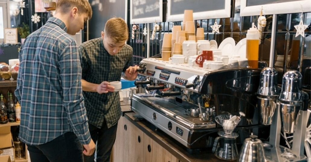 Two young boys using a coffee machine at a cafe.