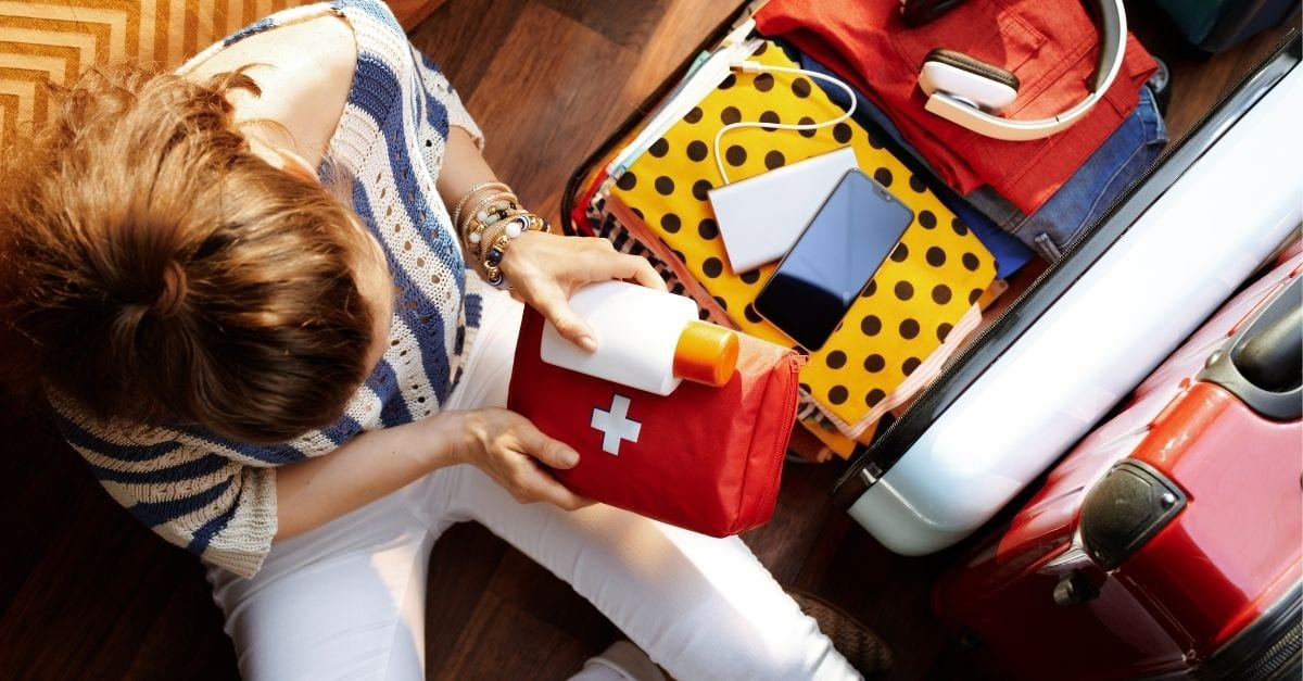 Top view of a young woman packing a first aid kit into her travel luggage.