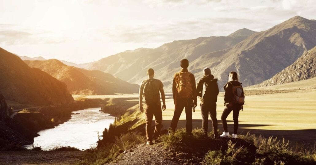 A group of four friends contemplating a mountainous National Park after hiking, at dawn.