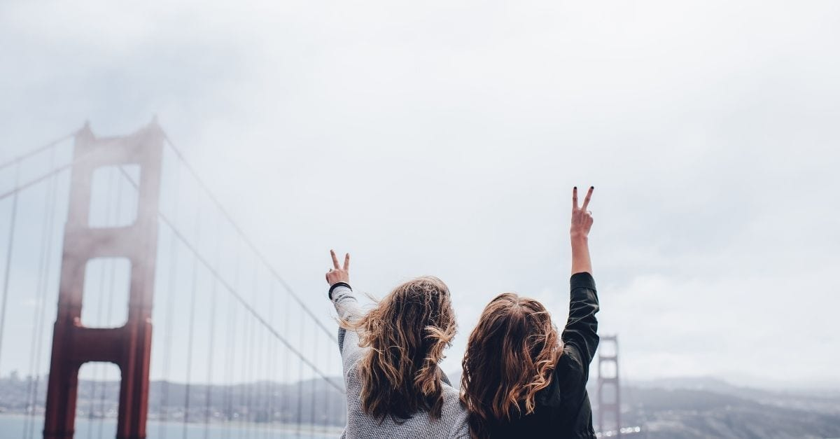 Mom and daughter doing the peace sign in front of the Golden Gate Bridge, in San Francisco.