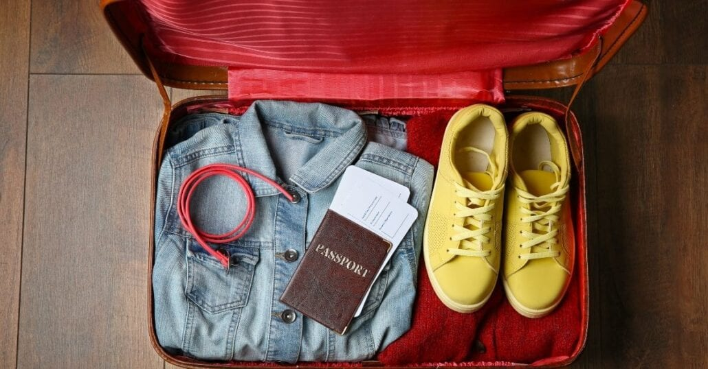 A jacket, an USB cable, a passport and a pair of yellow snickers inside a travel suitcase.