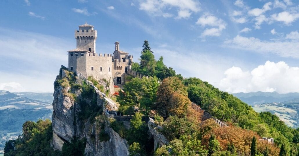 View of the Three Towers of San Marino over a green forested hill.