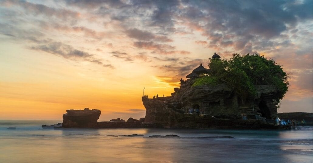 View of the Tanah Lot Temple, in Bali, during an orange sunset.