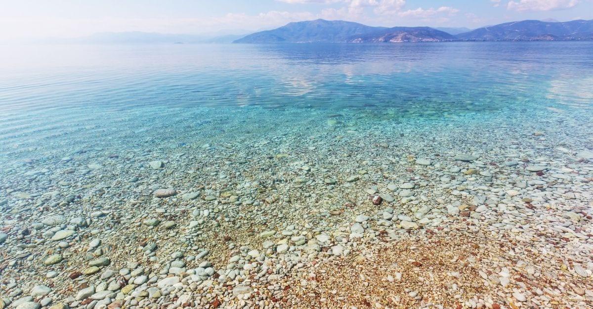 A trasparent blue-green ocean on a pebbly beach.