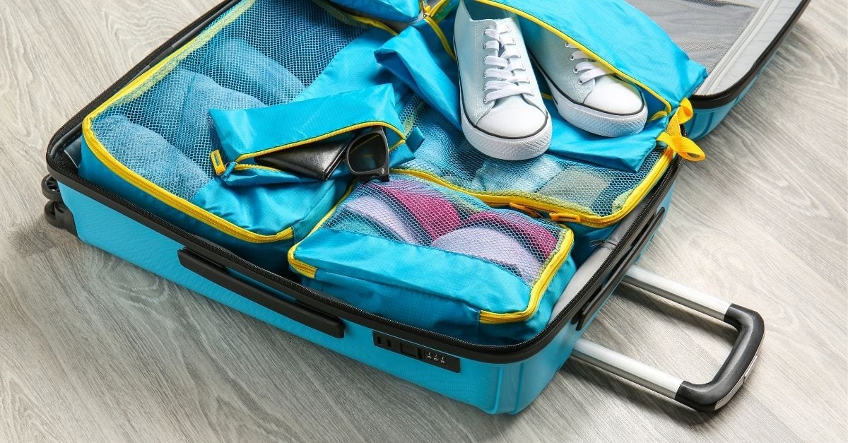 Personal items organized inside packing cubes in a travel suitcase.