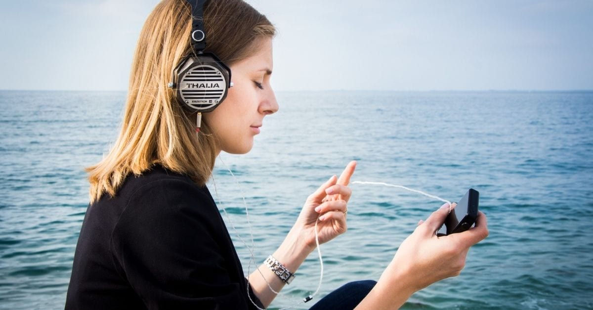 Woman listening to a travel podcast in front of the ocean.
