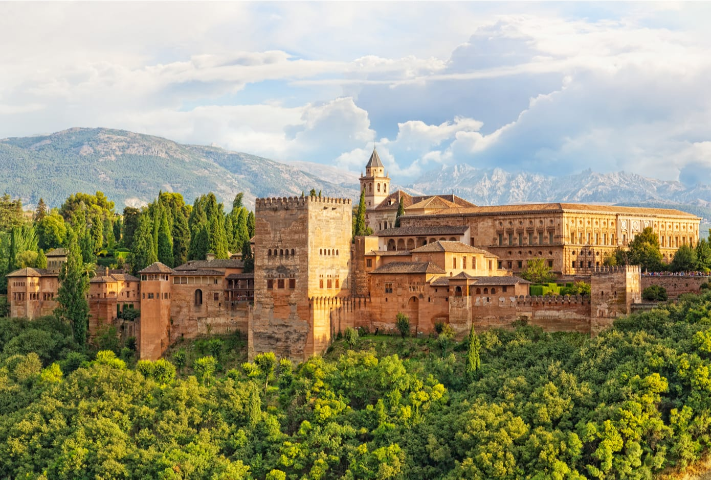 The ancient Alhambra fortress surrounded by a forest in Granada, Spain.