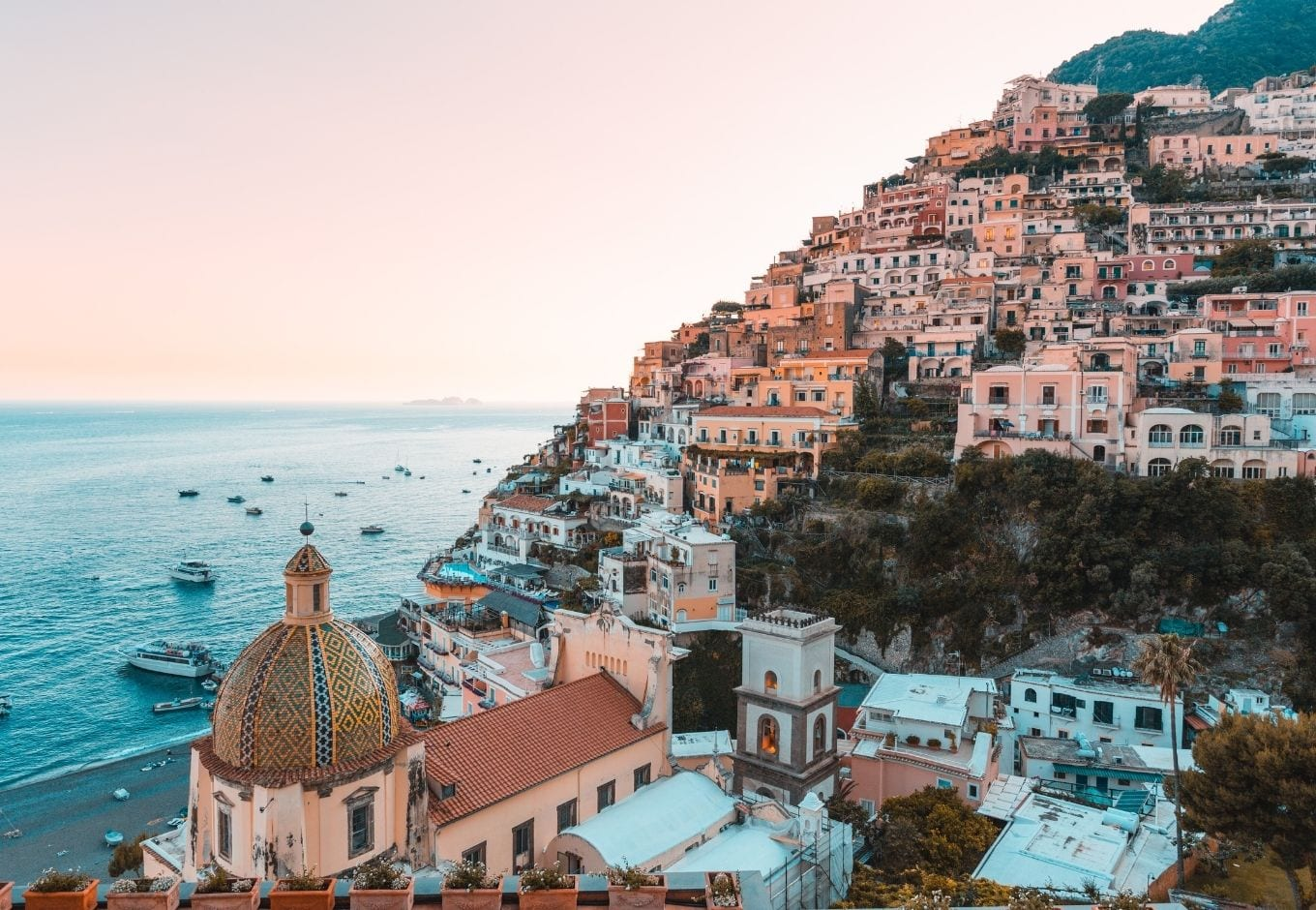 The Amalfi Coast dotted with pink-hued houses at dusk.