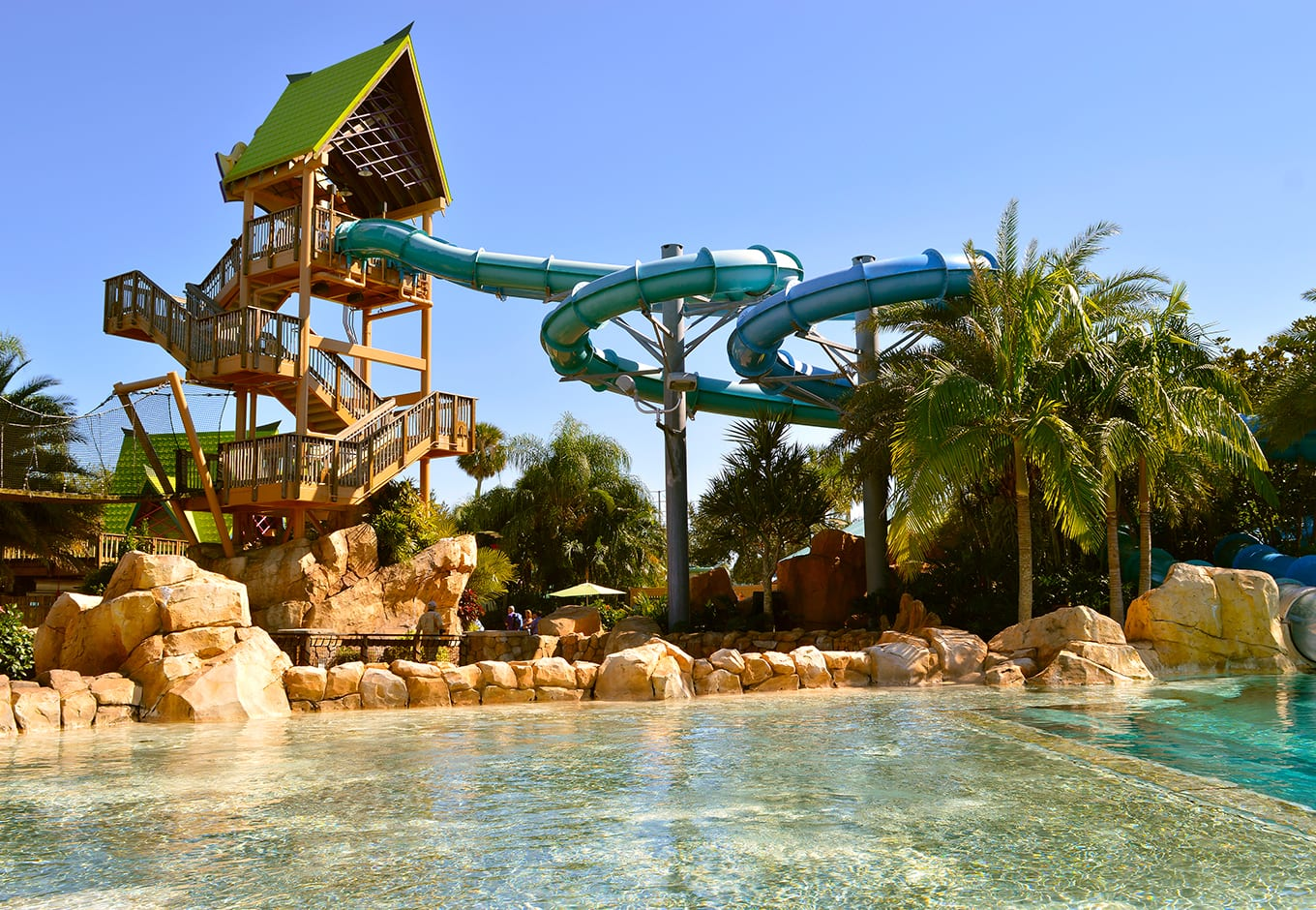 View of ttwo waterslides and a pristine pool surrounded by palm trees at the Aquatica Water Park, Orlando.