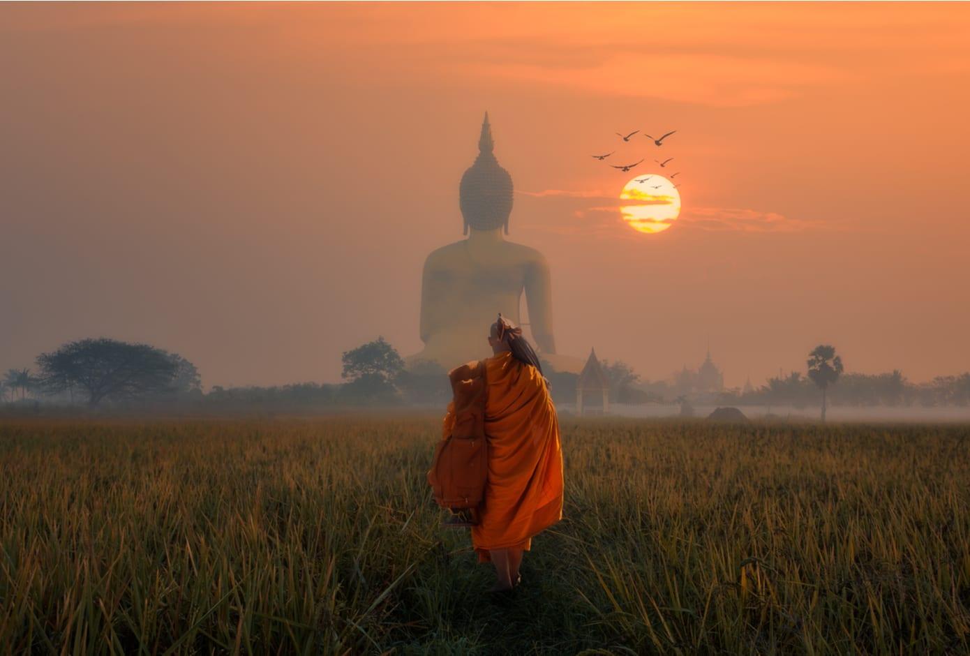 Monk walking towards the Big Buddha at Wat Muang Angthong, Thailand Temple at sunset.