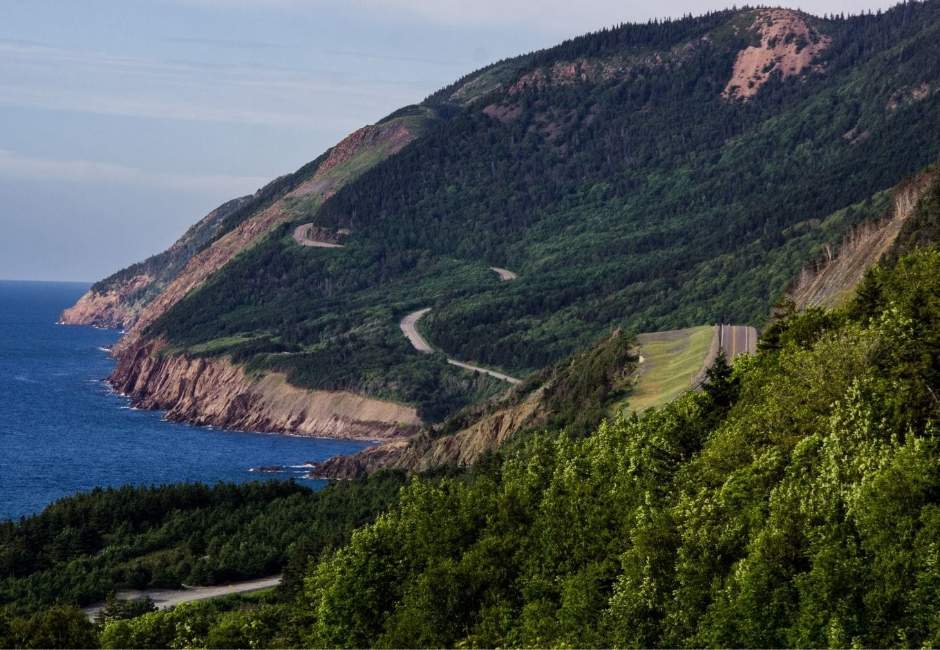 The Cabot Trail Road surrounded by green forests, at Nova Scotia.