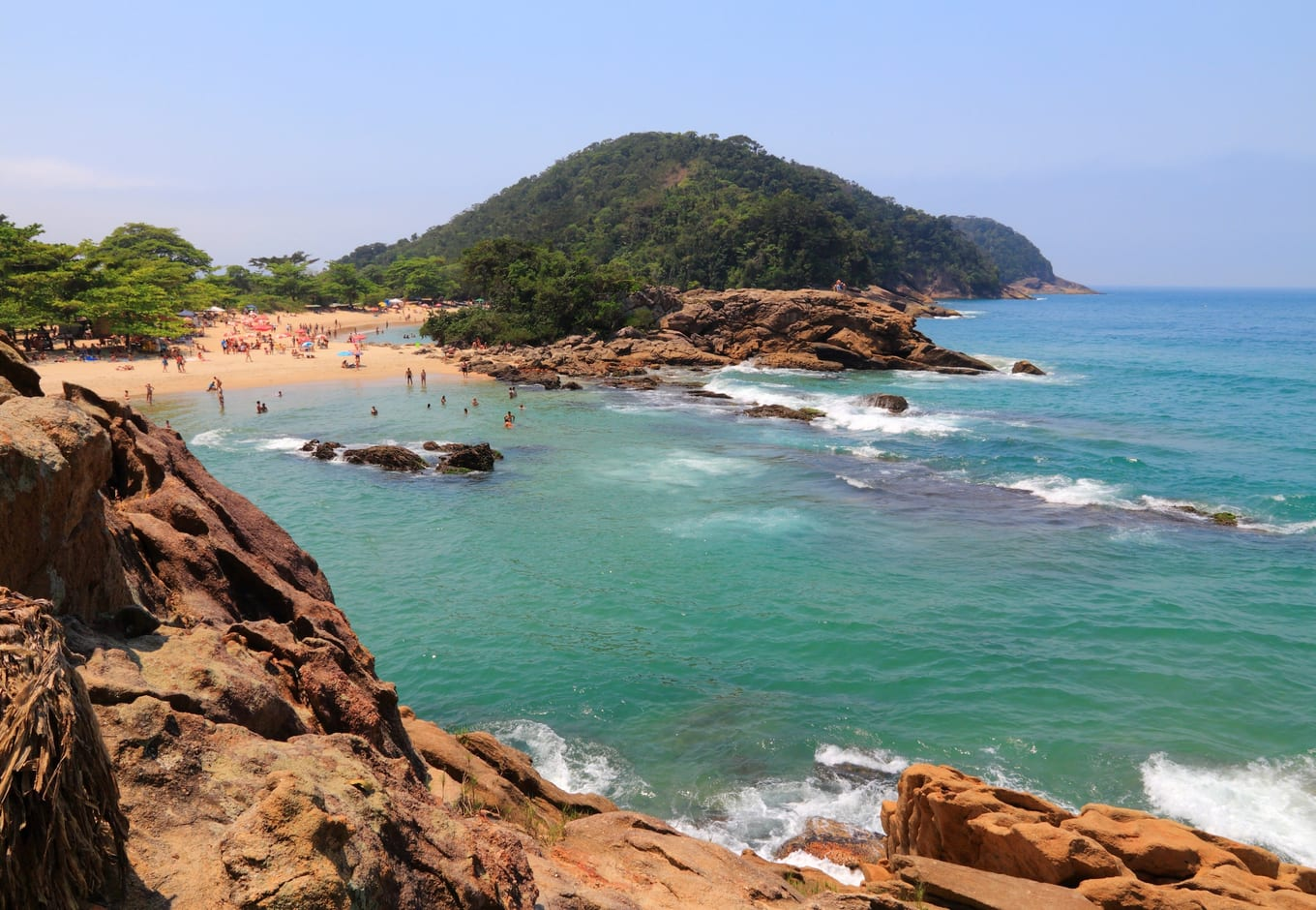 The blue-green ocean surrounded by rocks and a forested hill on Trindade Beach, Brasil.