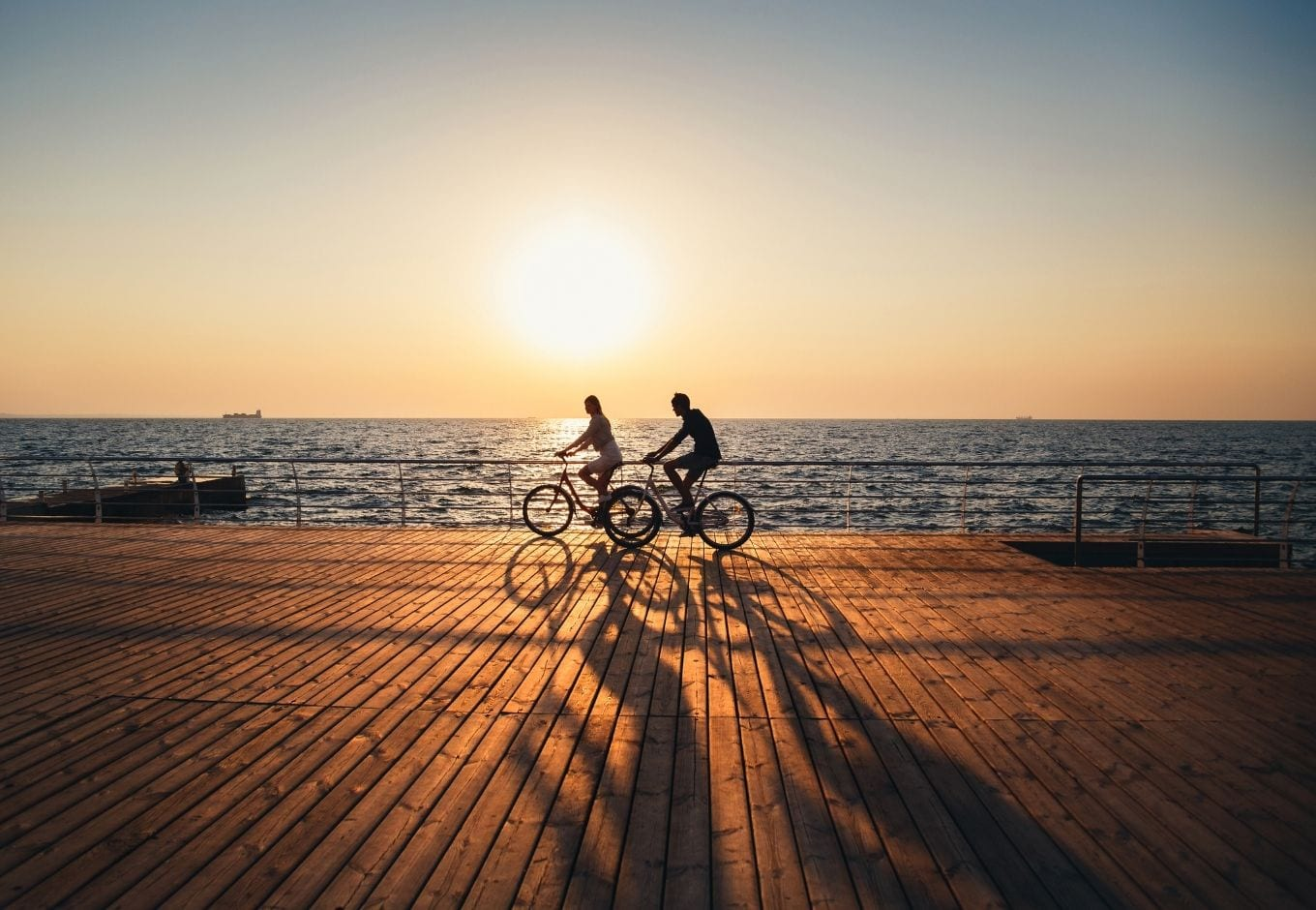 A woman and a man cycling over a wooden deck by the ocean at sunset.