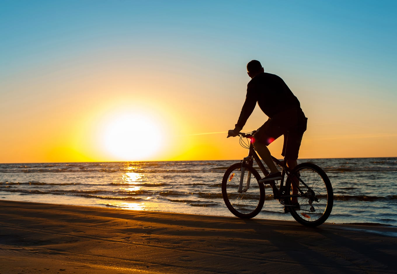 A man cyclist on the beach during the sunset.