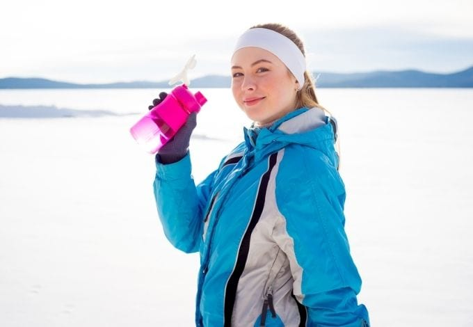 Young woman drinking water on a snowy mountain.