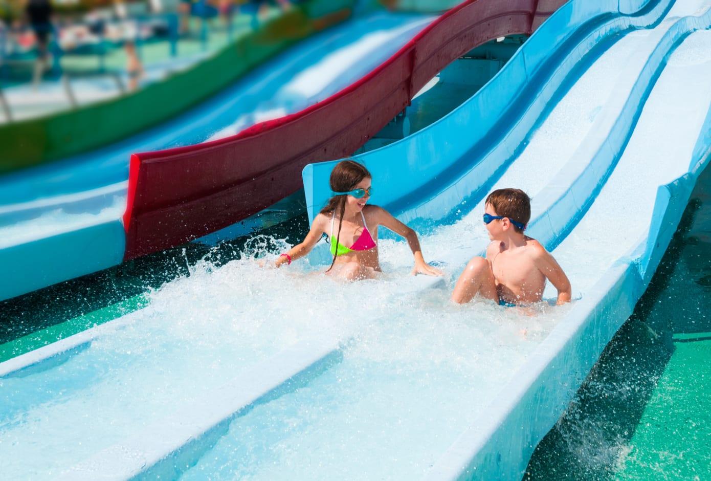 Two kids having fun at a water slide.