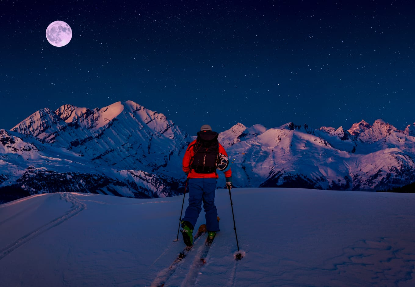 Night ski with view of the mountains and the full moon.