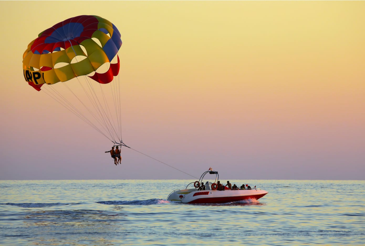 Two people parasailing above the ocean at sunset.