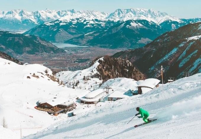 A person downhill skiing in a mountain.