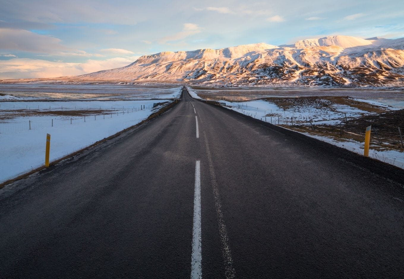 The Ring Road leading to a range of snowy mountains, in Iceland.