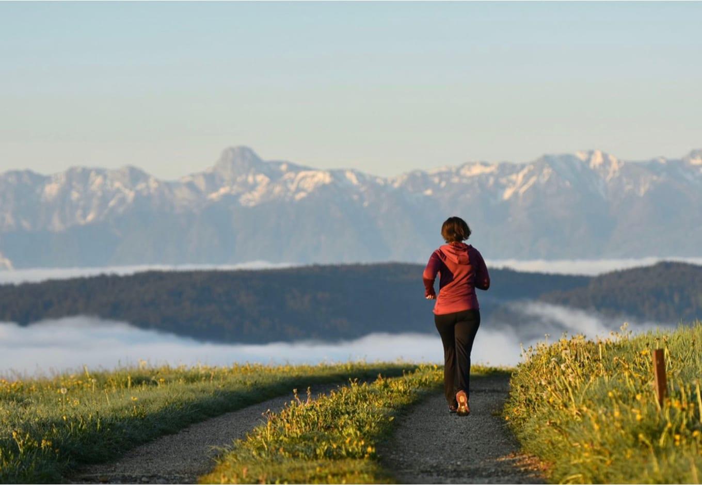 Woman running towars a snowy mountain range.