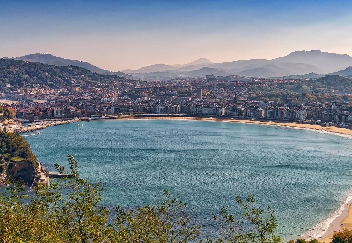 View of the ocean surrounded by buildings and mountains in San Sebastian, Spain.