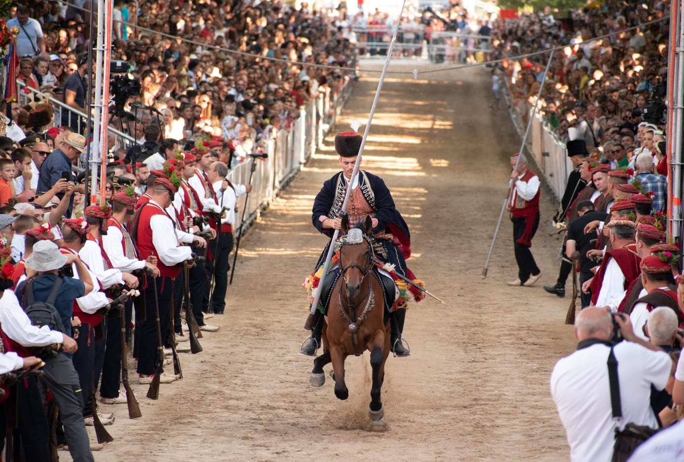 Alkar on his decorated horse galloping, hitting the metal ring  with his spear during Sinjska Alka, tournament, in Sinj
