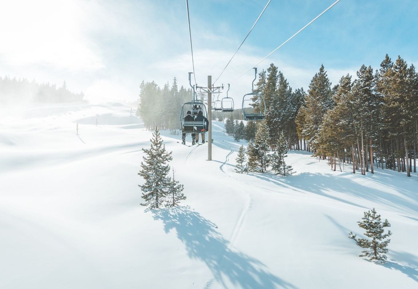 Ski lifts surrounded by snow and pine trees.