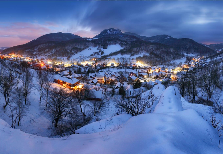 A snowy mountain ski village at night.