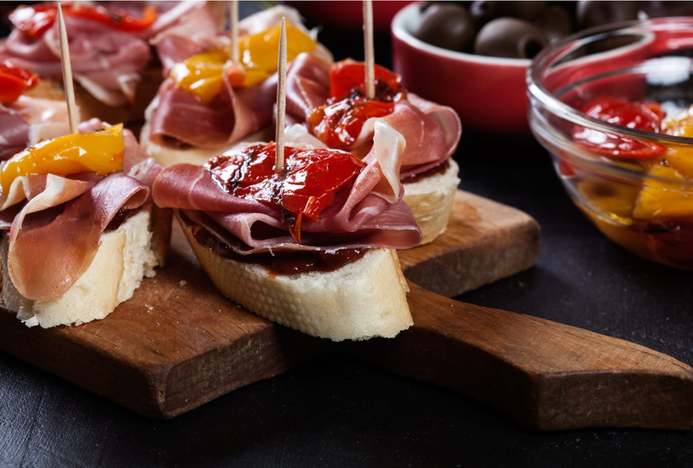 Spanish tapas with slices jamon serrano and grilled pepper.