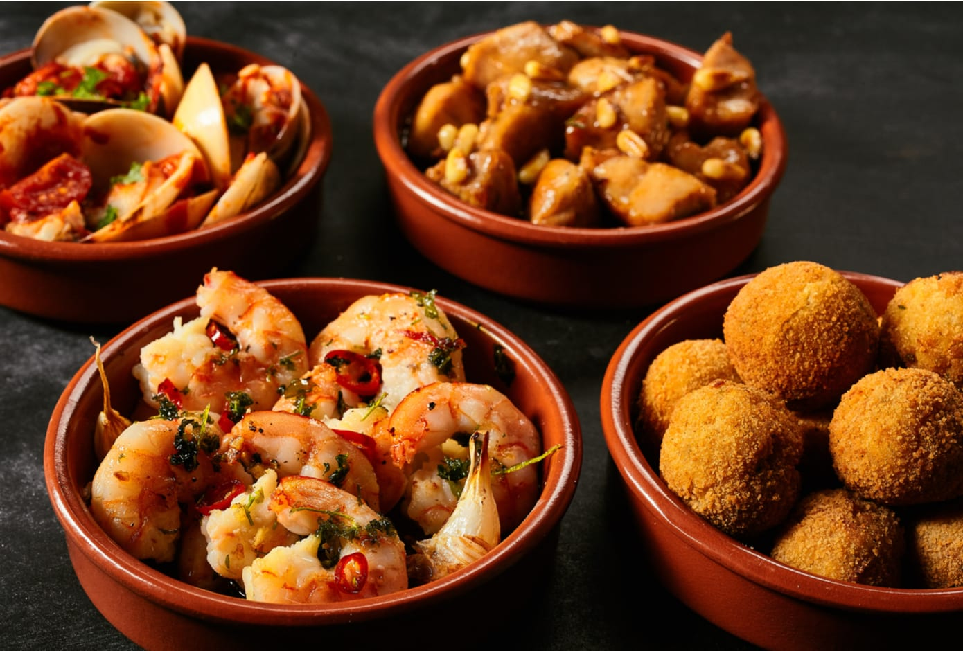 Four red ceramic bowls filled with Spanish tapas.