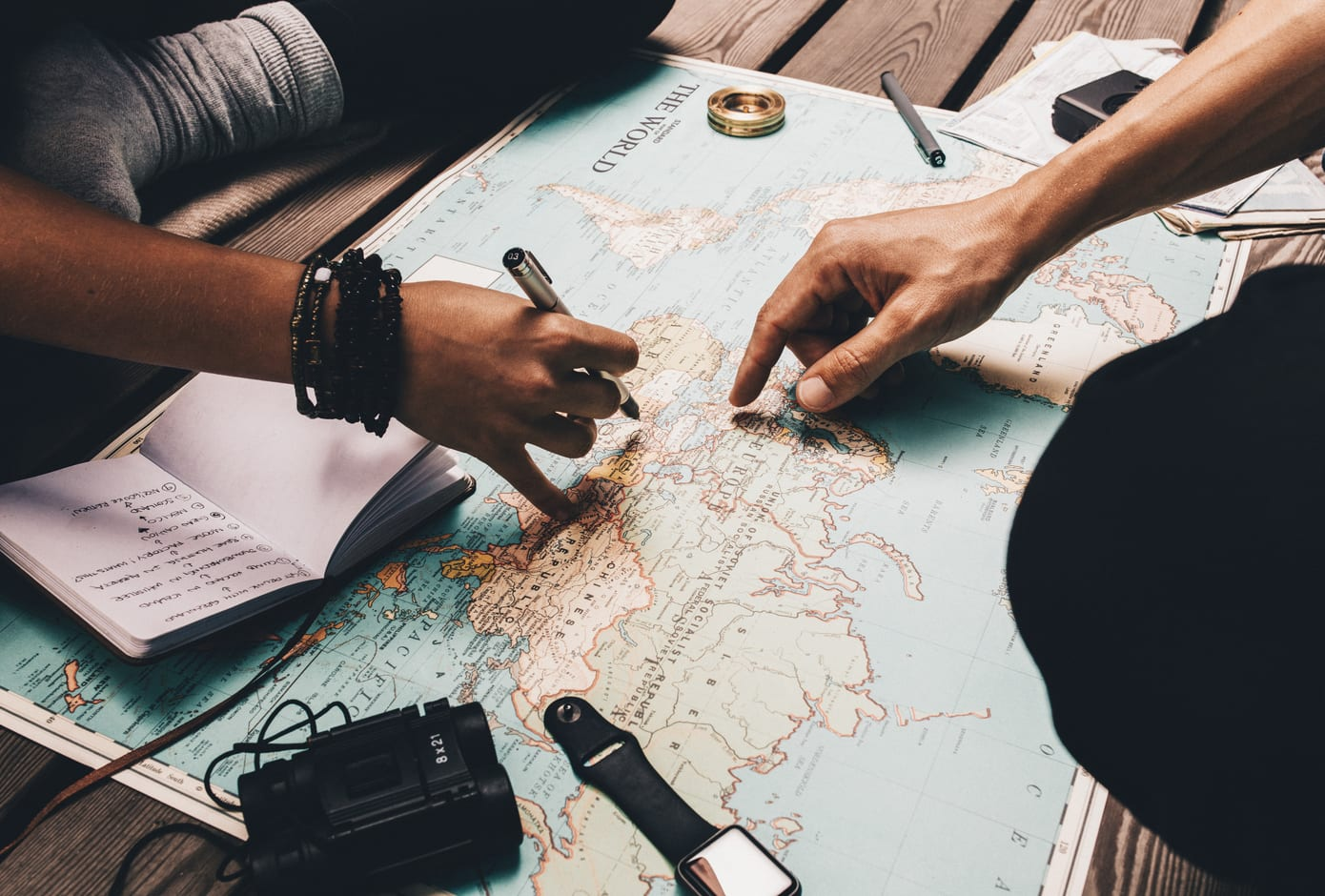 Two travelers pointing at a map and taking notes while planning a trip.
