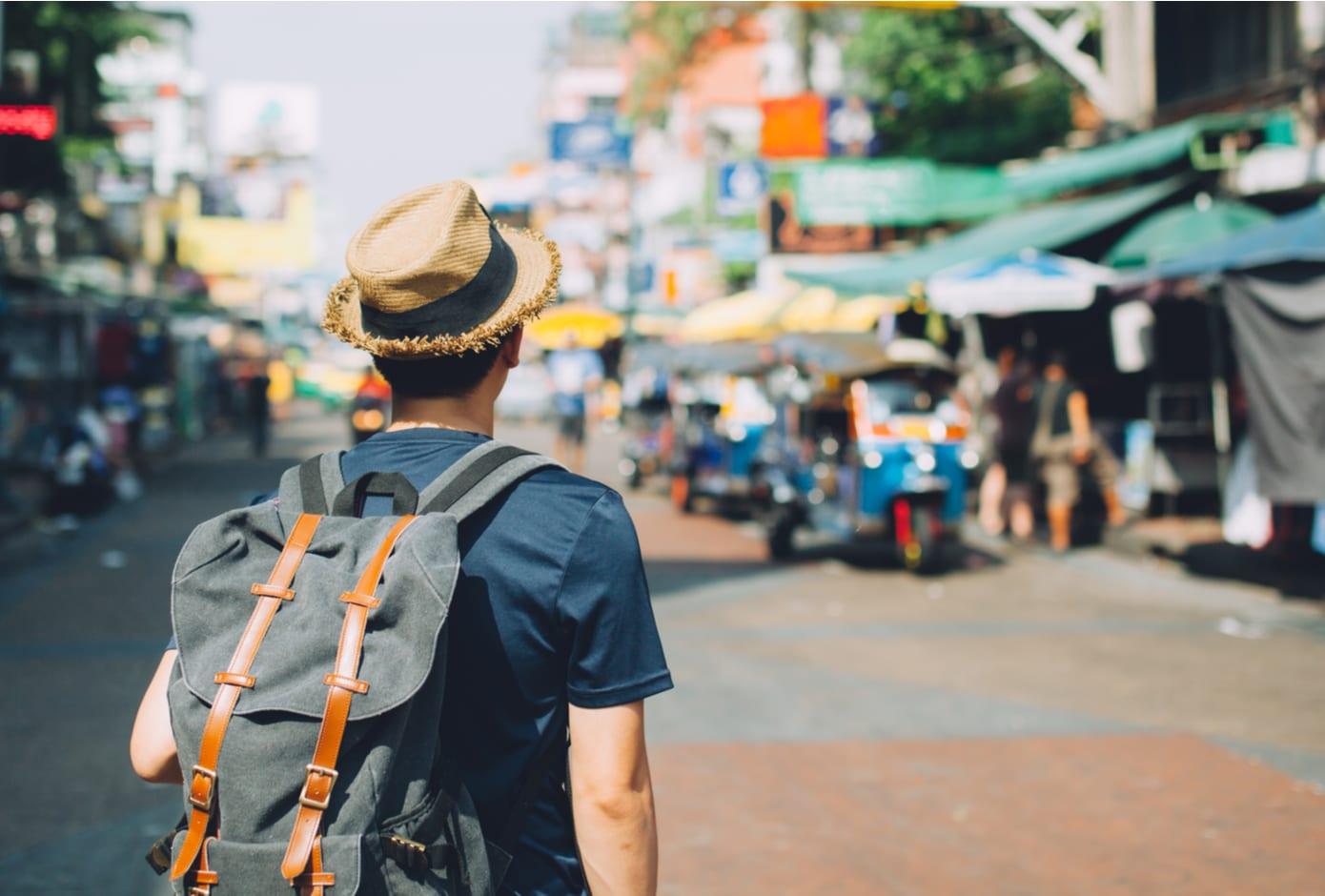 Young Asian backpacker at Khaosan Road outdoor market in Bangkok, Thailand