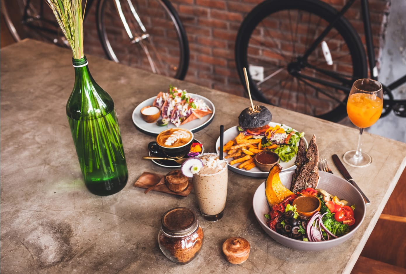 Fresh organic vegetarian food and glass of kombucha in hipster style cafe