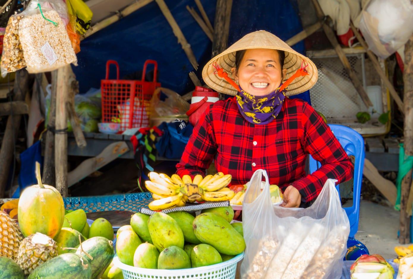 Smiling Vietnamese woman selling fruit on Sao Beach. Vietnam
