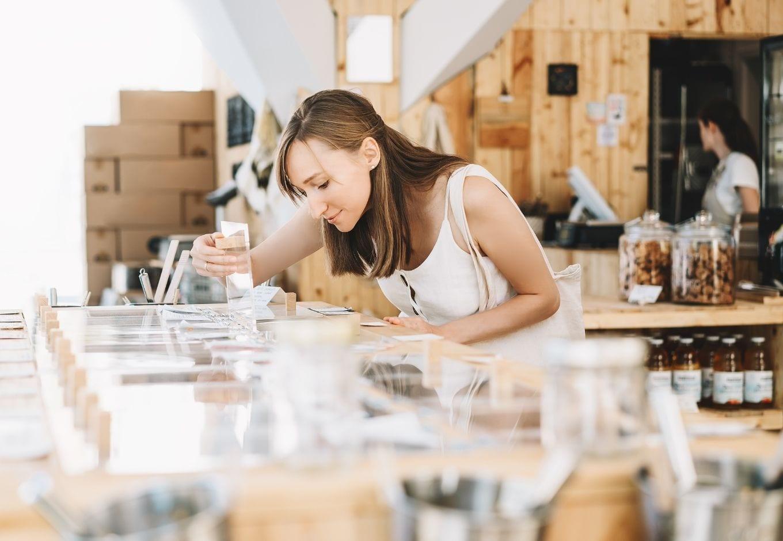 A woman choosing grains at an organic food store.