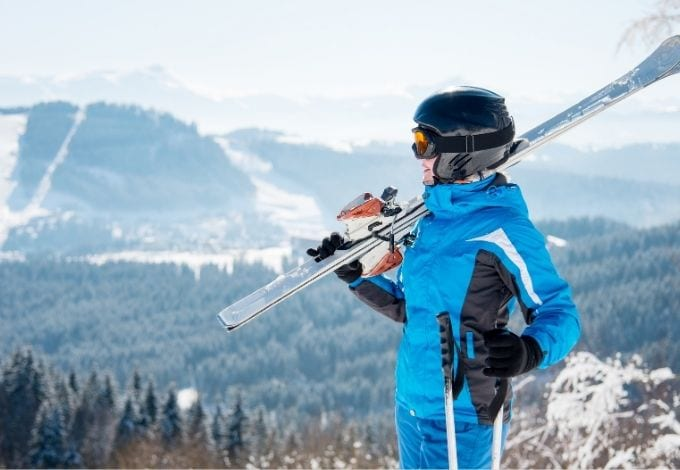 A happy woman holding her ski equipments on top of a mountain.