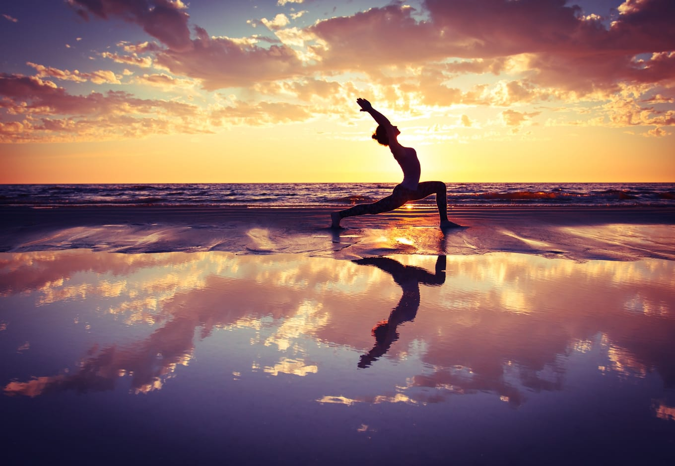 Woman practicing yoga at the beach.