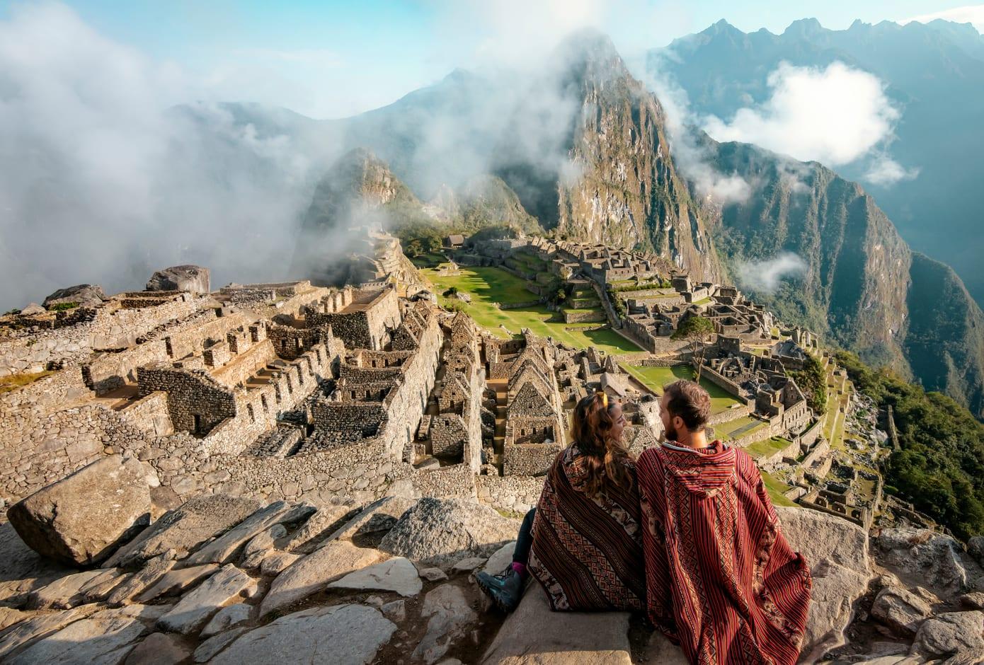 Couple dressed in ponchos in Machu Picchu, Peru.