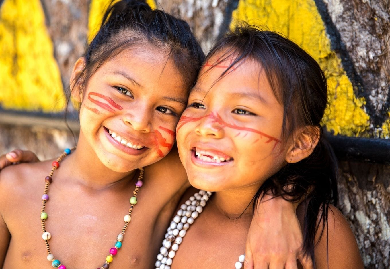 Portrait of two native Brazilian girls smilling.