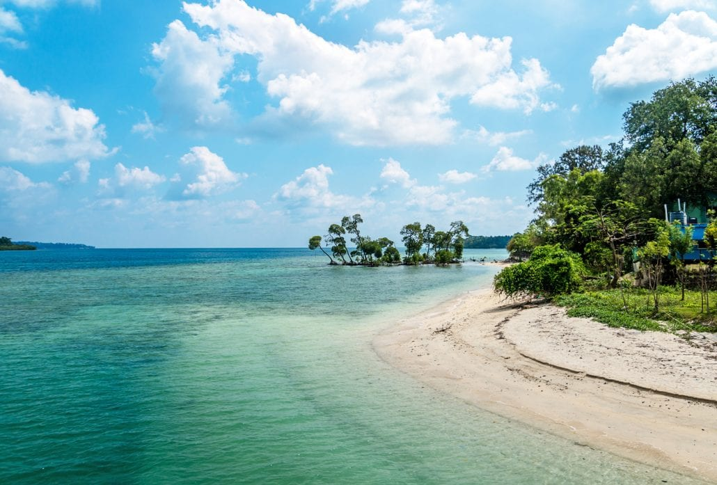 A white sand beach with transparent blue-green water in the  Andaman and Nicobar Islands, India.