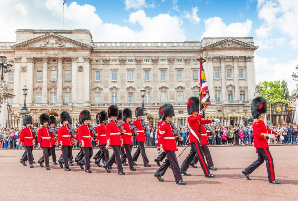 Some 20 guards marching in front of the Buckingham Palace while being watched by a crowd of people.