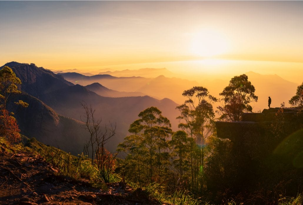 Silhouette of a woman watching the sunrise at Dolphin's nose in Kodaikanal, India.