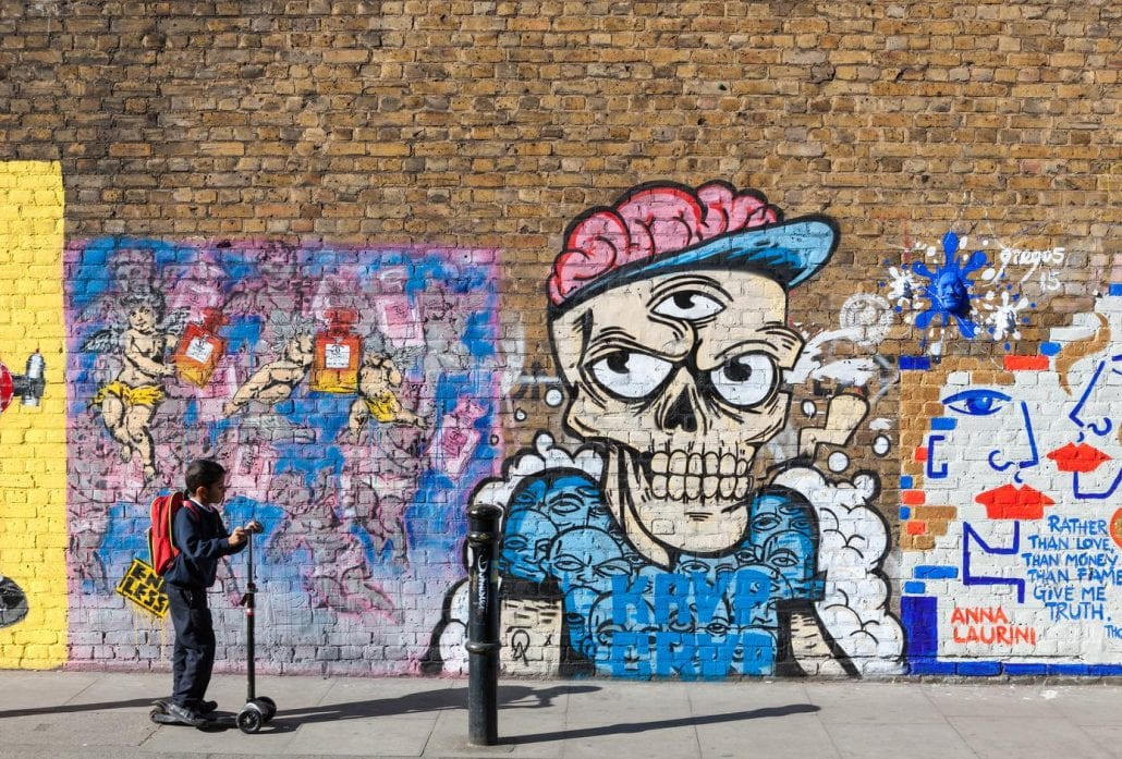 A kid in front of a street art mural in the trendy neighborhood of Shoreditch, London.